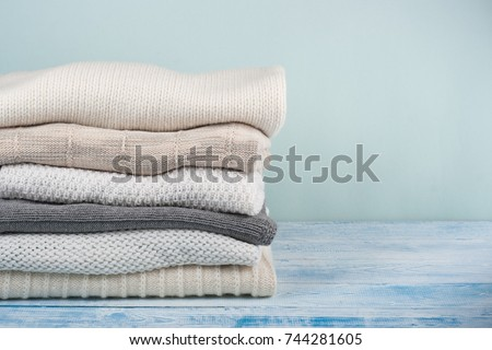knitted wool sweaters. pile of...