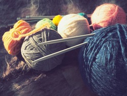 Knitting a scarf or sweater from gray, blue, white and orange yarns. Hanks of woolen and acrylic threads. Knitting as a hobby. Accessories, knitting needles, crochet hooks.