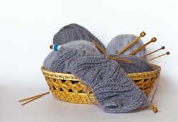 Knitting a warm gray scarf from wool and mohair yarn with bulky knitted braids. Balls of yarn and wooden knitting needles in a wicker basket on a white background. Winter knit, handicrafts and hobbies