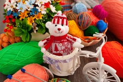 Knitting and a bear in knitted clothes. Multi-colored balls of yarn on a background of flowers. Bear in knitted clothes. Knitting as a kind of needlework.