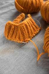 Knitting from bright orange wool yarn tangles with circular spokes on a gray background