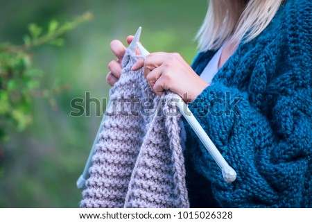 Knitting on knitting. Hands close-up knitting on knitting needles, gray wool knit against the backdrop of a natural garden. Needlework in the garden.