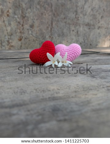 Knitting red and pink hearts with white Millingtonia on the rough wooden table. The background of rock wall with sun light. Copy space for editing #1411225703