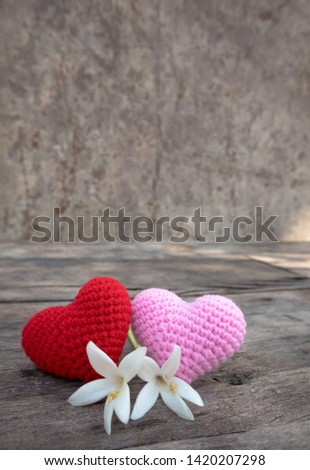 Knitting red and pink hearts with white Millingtonia on the rough wooden table. The background of rock wall with sun light. Copy space for editing #1420207298