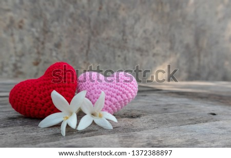 Knitting red and pink hearts with white Millintonia on the rough wooden table. The background of rock wall with sun light. Copy space for editing #1372388897