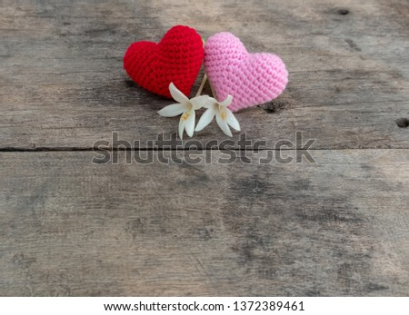 Knitting red and pink hearts with white Millintonia on the rough wooden table. The background of rock wall with sun light. Copy space for editing #1372389461
