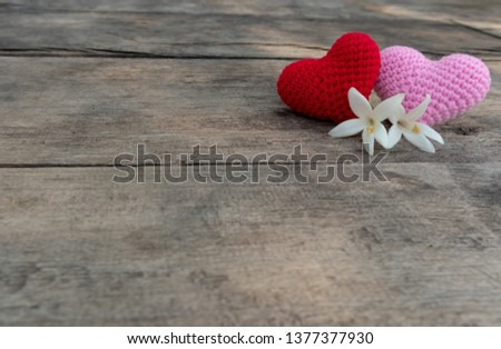 Knitting red and pink hearts with white Millintonia on the rough wooden table. The background of rock wall with sun light. Copy space for editing #1377377930
