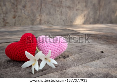 Knitting red and pink hearts with white Millintonia on the rough wooden table. The background of rock wall with sun light. Copy space for editing #1377377933