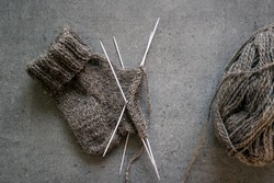 Knitting socks, work in progress. top view photo of wool yarn, knitting needles and half of handmade sock. Grey textured background.  Winter hobbies.