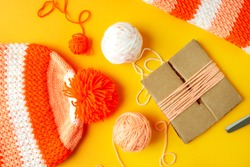 Knitting warm hat. View from above. Knit warm clothes for cold seasons. Pompon from yarn for knitted hat. Yarn on a yellow background.