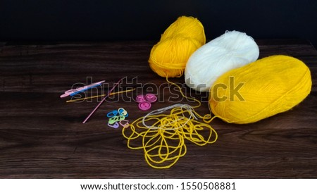 knitting white and yellow balls with crocheting accessories .crocheting accessories are hooks,needles and buttons on a wooden table.close up shot