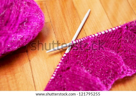 knitting wool and knitting needles on wooden background