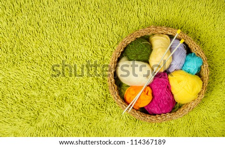 Knitting yarn balls and needles in basket over green carpet background - stock photo