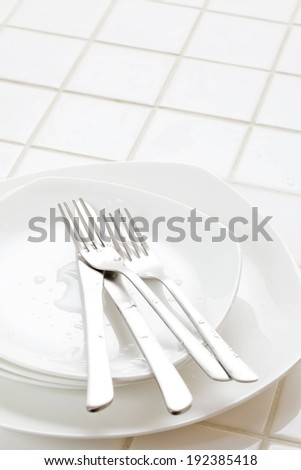 Knives and forks on a small plate that sits on other plates.
