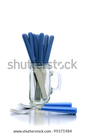 Knives in a mason jar glass with handle and a fork and spoon on the table top in front. Vertical format over white with reflection.