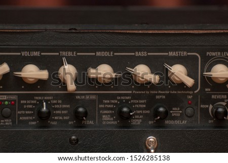 knobs of various adjustments of a classical guitar amp
