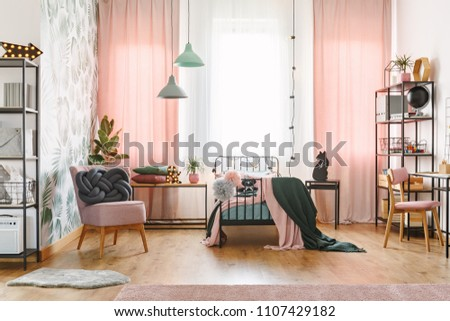Knot pillow on pink armchair in pastel girl's bedroom interior with lamps and drapes