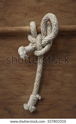 Knot tied around a wooden rail on a wooden background