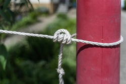 Knot with a white cord around a lamppost (close-up)