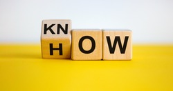Know how and business concept. Turned cube and changed the word 'how' to 'know'. Beautiful yellow table, white background. Copy space.
