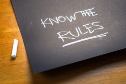 KNOW THE RULES text, handwriting as a note on black paper on the table