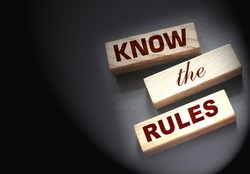 Know the rules word on wooden blocks isolated on dark grey background. business process regulation concept.
