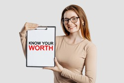 KNOW YOUR WORTH. Beautiful young business woman wearing glasses holds a clipboard with mock up space isolated on gray background