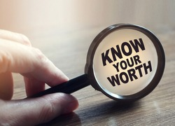 Know Your Worth under Magnifying glass on wooden table. Career concept. Self motivation coaching HR concept.