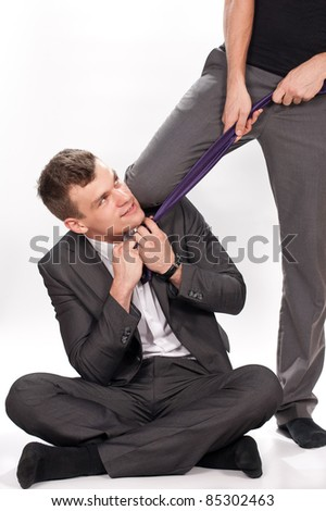 knowing businessman slightly smiling while being pulled by the tie, conceptual
