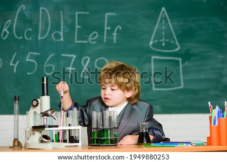 Knowledge concept. Kid study biology chemistry. Knowledge day. Basic knowledge primary school education. Happy childhood. Child enjoy studying. Boy near microscope and test tubes in school classroom Photo stock ©