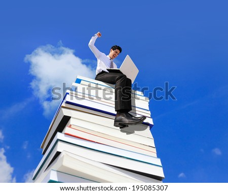 Knowledge is power - Happy business man using pc computer and sitting on a stack Of Books