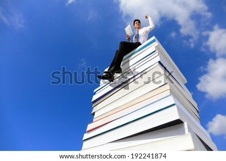 Knowledge is power - Happy business man using tablet pc computer and sitting on a stack Of Books