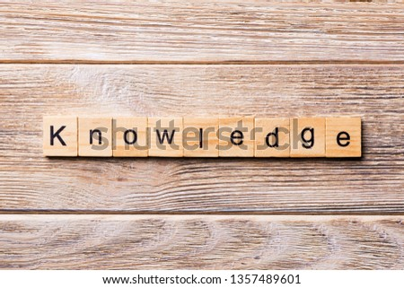 Knowledge word written on wood block. Knowledge text on wooden table for your desing, concept.