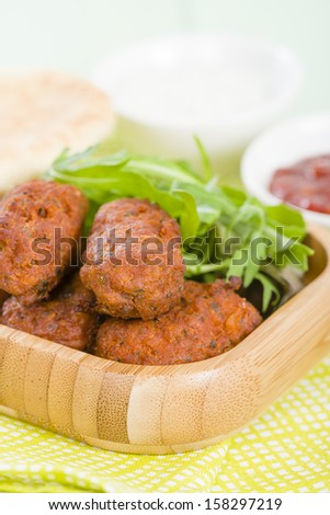 Koftas - Asian style meatballs served with salad and pita bread, chili sauce and yoghurt. - stock photo