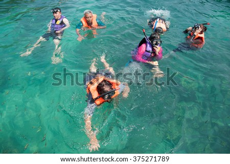 Koh Ngai, Thailand March 19, 2015: Tourists enjoy the beach and the beautiful and wide and Koh Ngai surrounded by the natural beauty of the islands in Trang province, Thailand  #375271789