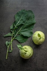 Kohlrabi and kohlrabi leaves on a dark background