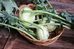 Kohlrabi cabbage on a wooden table, basket