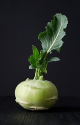 Kohlrabi or french turnip over black wooden table
