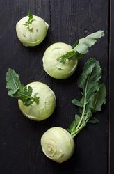 Kohlrabi or french turnips over black wooden table