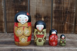 Kokeshi. Vintage russian matryoshka (set of nested dolls) as ancient national craft of Japan. Japanese traditional folk wooden doll: kokeshi. Souvenir from Japan. Ethnic handicraft. Japanese folk art