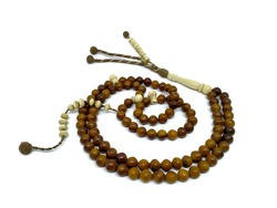 Kokka prayer beads are placed in a circular shape. This kokka wooden prayer beads has a total of 100 pieces. This coca wood prayer beads in the photo above the white background.
