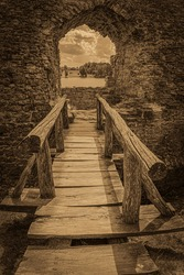 Koknese Castle is a complex in Koknese, Latvia, dating from the 13th century. Wooden bridge to old ruined window. Monochrome, sepia.