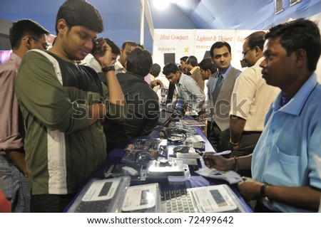 KOLKATA- FEBRUARY 20:  A customer talks on his mobile phone  during the Information and Communication Technology (ICT) conference and exhibition in Kolkata, India on February 20, 2011. - stock photo