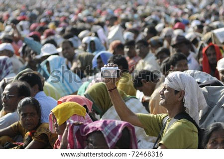 KOLKATA- FEBRUARY 13:  A man filming the crowd and the ambiance  during a political rally  in Kolkata, India on February 13, 2011.