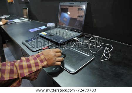 KOLKATA- FEBRUARY 20: A  man tries to use the pen & touch pad, during the Information and Communication Technology (ICT) conference and exhibition in Kolkata, India on February 20, 2011.