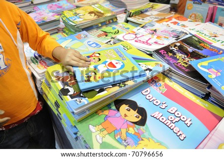 KOLKATA- FEBRUARY 4: A small kid grabs a cartoon book during the 2011 Kolkata Book Fair in Kolkata, India on February 4, 2011.