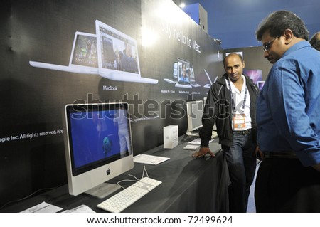 KOLKATA- FEBRUARY 20: A visitor looks towards a MAC computer during the Information and Communication Technology (ICT) conference and exhibition in Kolkata, India on February 20, 2011.