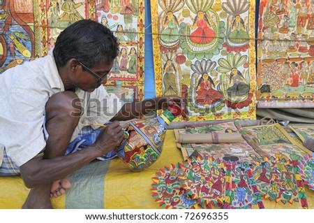 KOLKATA- FEBRUARY 23:  An old man painting a pottery ,during the Handicraft Fair on February 23, 2011 in Kolkata, India.