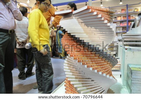 "KOLKATA- FEBRUARY 4: An unidentified kid looks at stacks of the book called ""the monk who sold his ferrari"" during the 2011 Kolkata Book Fair in Kolkata, India on February 4, 2011."