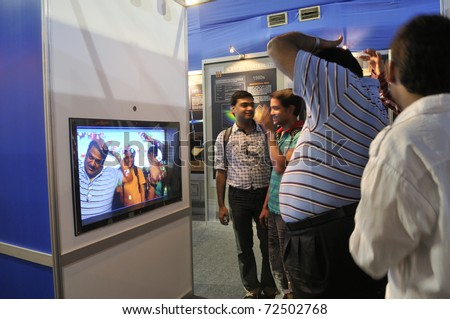 KOLKATA- FEBRUARY 20:  Visitors watching themselves in a bubble screen,during the Information and Communication Technology (ICT) conference and exhibition on February 20, 2011 in Kolkata, India.